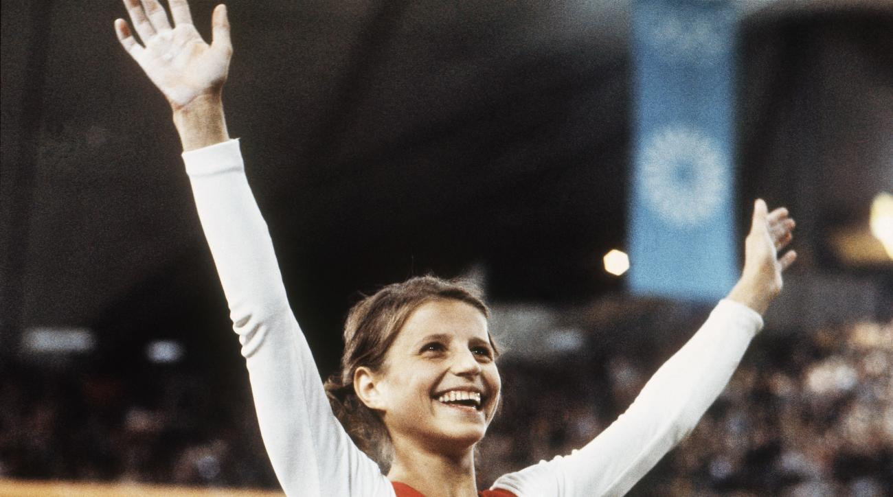 In this Aug. 1972, file photo, Olga Korbut, of Russia, throws up her arms in joy after winning the Individual Women's Gymnastic event at the 1972 Summer Olympics in Munich, Germany, Aug. 1972. At at 61, Korbut is at ease with her place in history as she e