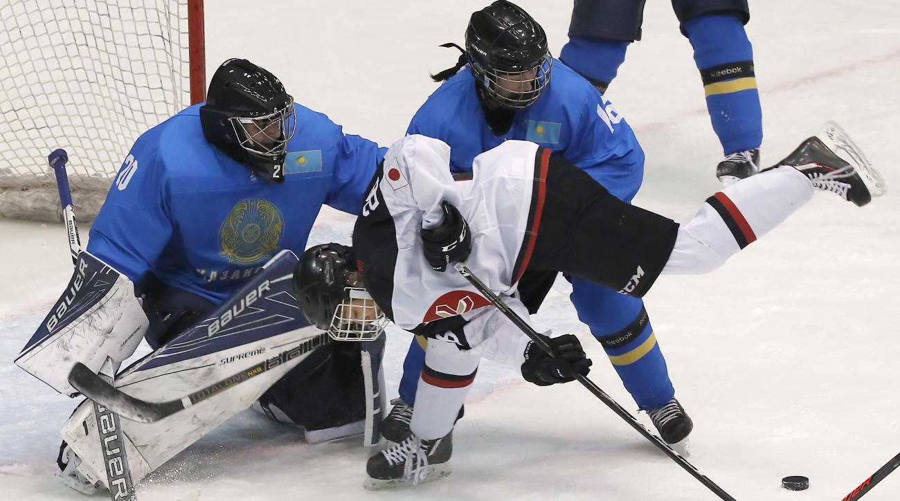Japan's Yoshino Enomoto, white jersey, tries to get through Kazakhstan's Olga Konysheva (16) and goalie Darya Dmitriyeva, left, during the women's tournament round robin ice hockey match at the Asian Winter Games at Tsukisamu Gymnasium in Sapporo, norther