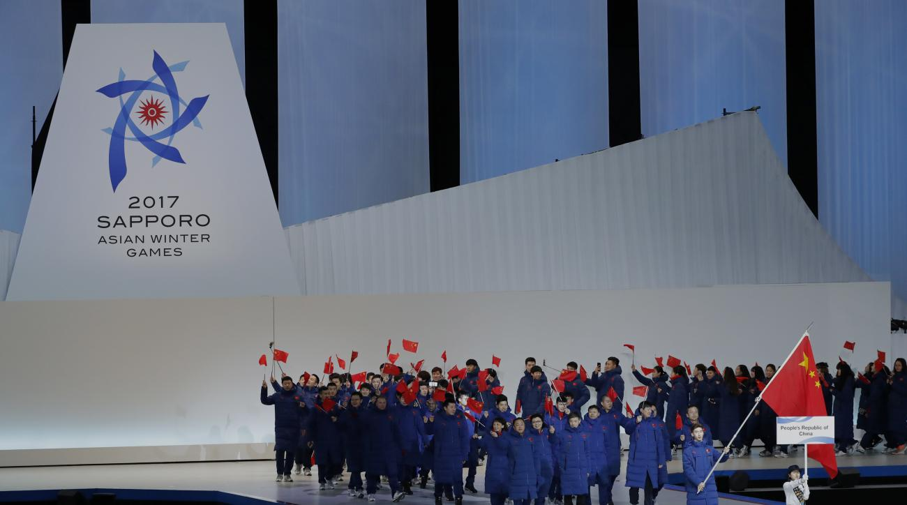 Members of Chinese team wave their national flags as they march at the opening ceremony of the Asian Winter Games at Sapporo Dome in Sapporo, northern Japan, Sunday, Feb. 19, 2017. (AP Photo/Eugene Hoshiko)