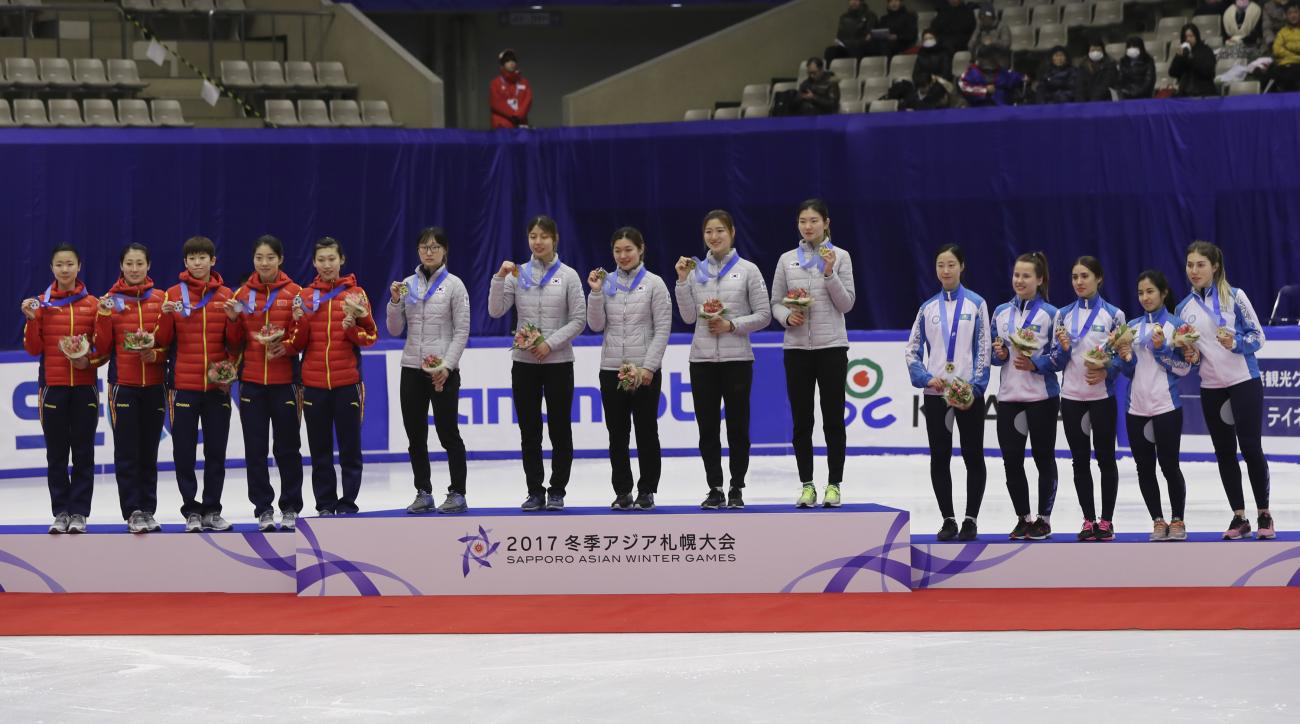 Gold medalists of South Korean team, center, pose with silver medalists of China, left, and bronze medalists of Kazakhstan, right, during the victory ceremony of the women's 3000 meter relay of short track speed skating competition at the Asian Winter Gam