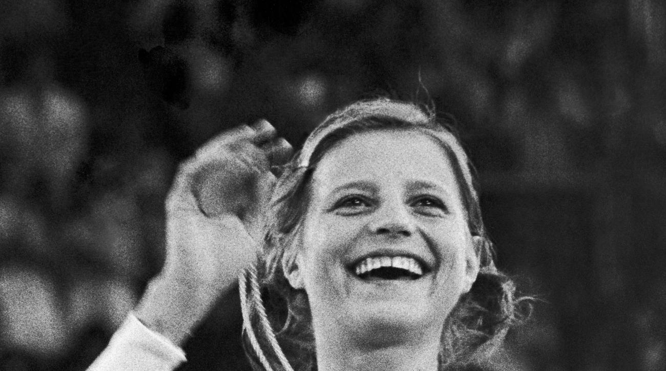 FILE - In this Aug. 31, 1972, file photo, Olga Korbut, USSR, holds up her gold medal in the gymnastics individual event at the summer Olympics in Munich. (AP Photo/Pool, File)