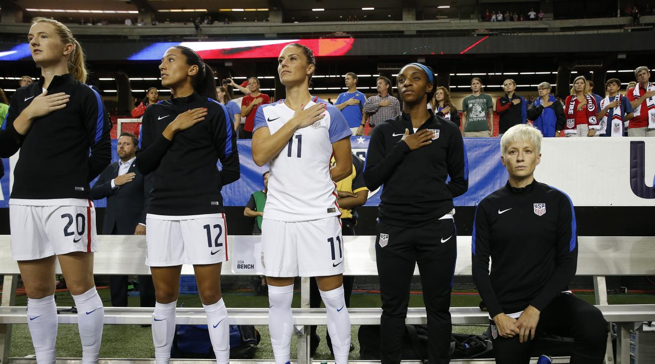 USA's Megan Rapinoe, right, kneels next to teammates Samanth Mewis (20) Christen Press (12), Ali Krieger (11), Crystal Dunn (16) and Ashlyn Harris (22) as the US national anthem is played before an exhibition soccer match against Netherlands Sunday, Sept.