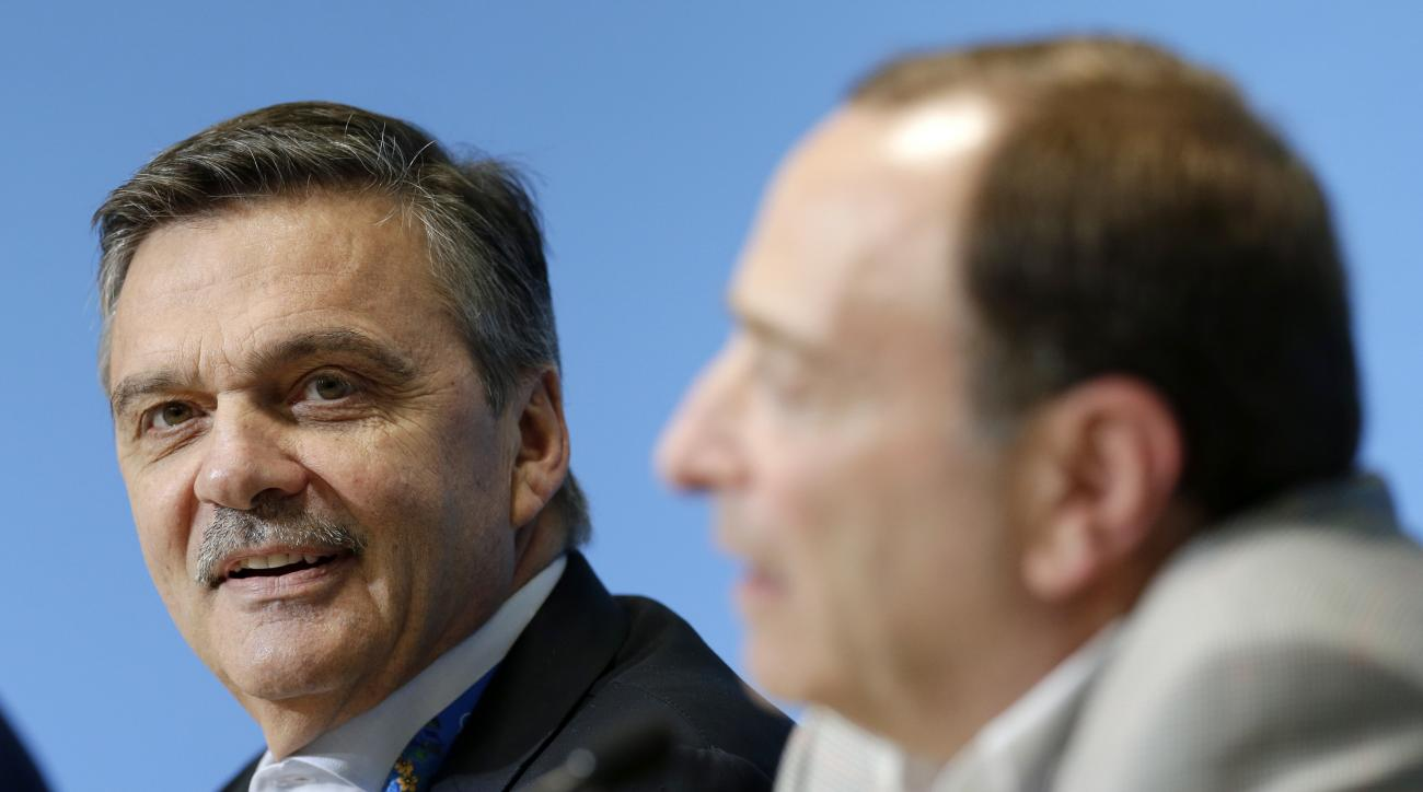 FILE - In this Feb. 18, 2014, file photo, International Ice Hockey Federation President Rene Fasel, left, listens as NHL Commissioner Gary Bettman, right, answers a question during a news conference addressing hockey issues at the 2014 Winter Olympics in