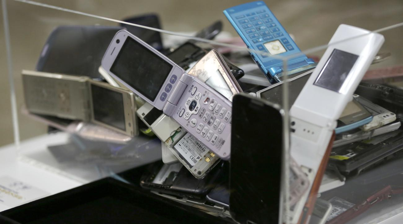 Gold tablets of 3 grams, left, which is able to be recycled from 100 mobile phones, are shown as example in Tokyo, Saturday, April 1, 2017. Organizers of the 2020 Tokyo Olympics began Saturday collecting discarded electronic devices that will be used in t