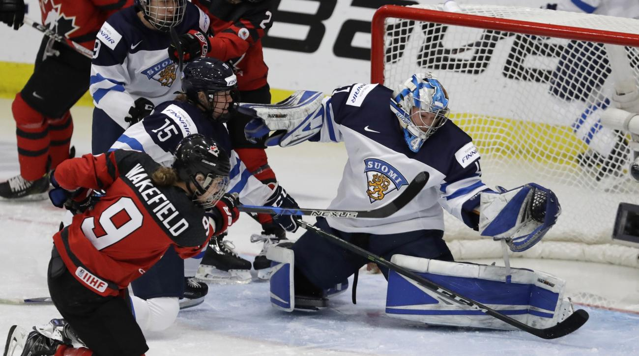 Finland goalie Noora Raty deflects a shot by Canada forward Jennifer Wakefield (9) during the first period of an IIHF women's world hockey championship semifinal game, Thursday, April 6, 2017, in Plymouth, Mich. (AP Photo/Carlos Osorio)