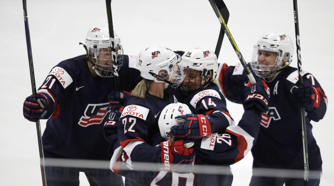 Players congratulate U.S. defender Kacey Bellamy (22) after her goal during the first period against Canada in the gold-medal game of the women's world hockey championships, Friday, April 7, 2017, in Plymouth, Mich. (AP Photo/Carlos Osorio)