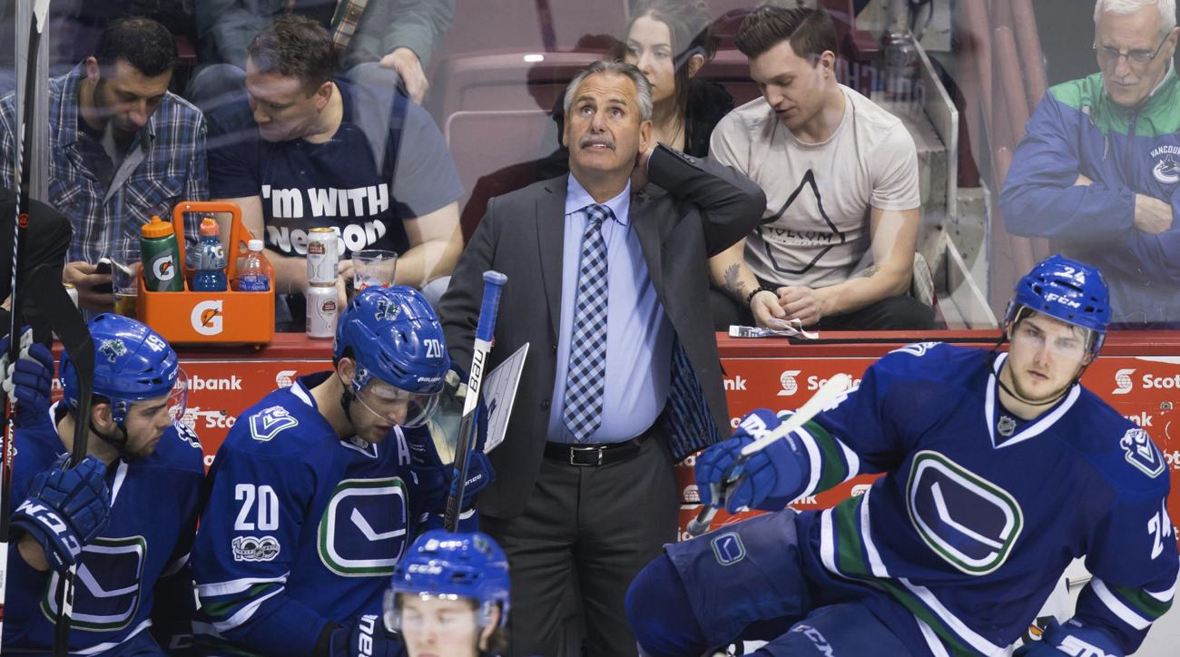Vancouver Canucks coach Willie Desjardins, back, stands on the bench behind Michael Chaput, Brandon Sutter and Reid Boucher during the third period of an NHL hockey game against the Edmonton Oilers on Saturday, April 8, 2017, in Vancouver, British Columbi