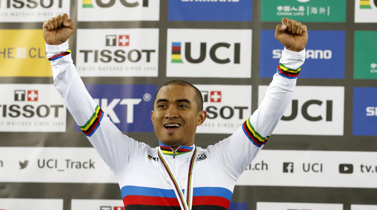 Malaysia's Azizulhasni Awang celebrates on the podium after winning the men's keirin final at the World Track Cycling championships in Hong Kong, Thursday, April 13, 2017. (AP Photo/Kin Cheung)