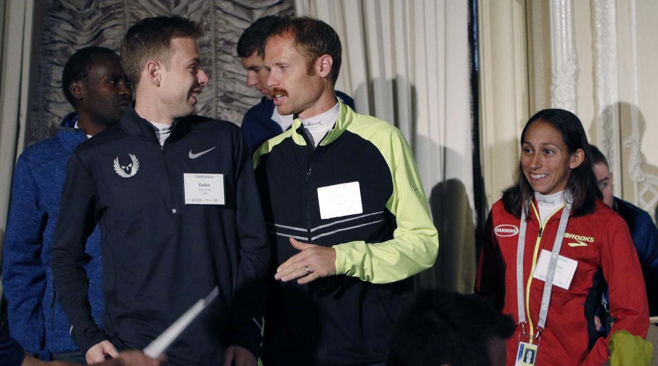 U.S. distance runners Galen Rupp, left front, Jared Ward, center, and Desiree Linden depart after a Boston Marathon media availability Friday, April 14, 2017, in advance of Monday's race in Boston. (AP Photo/Bill Sikes)