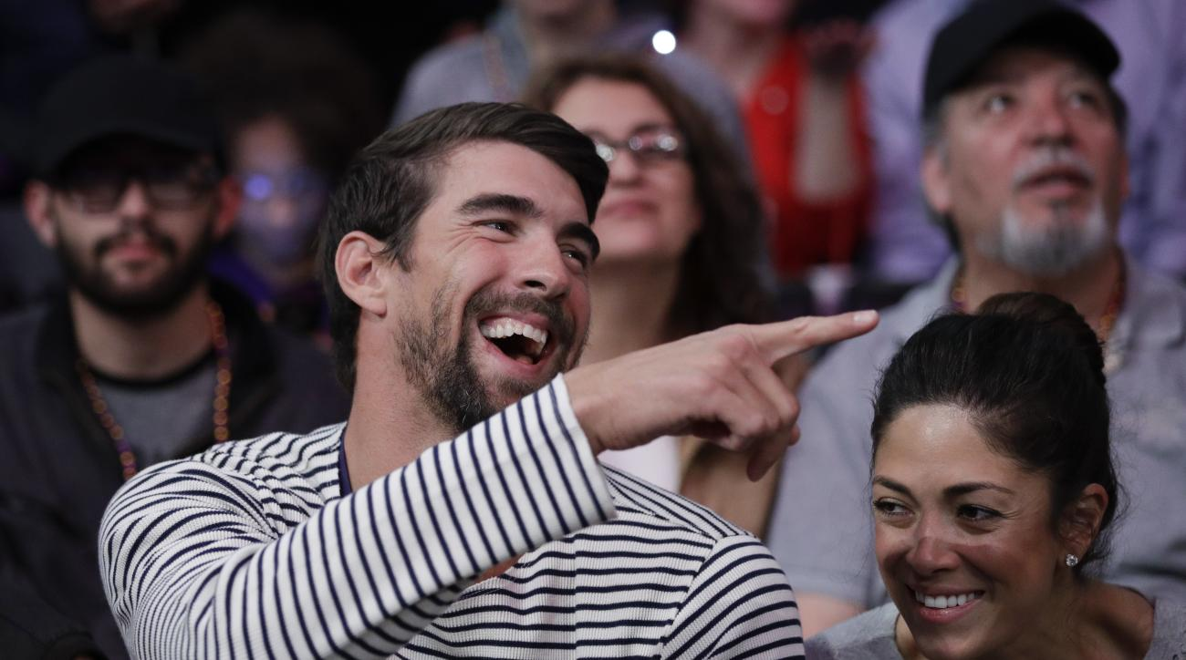 FILE - In this March 21, 2017, file photo, Michael Phelps and his wife, Nicole Johnson, smile during an NBA basketball game between the Los Angeles Lakers and the Los Angeles Clippers in Los Angeles. If Phelps returns to competitive swimming, the demands