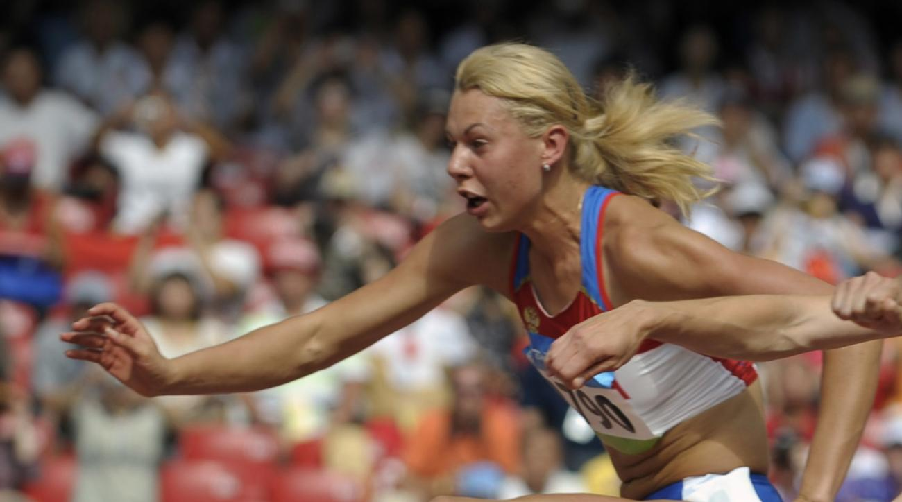 FILE - In this Aug. 15, 2008 file photo Russia's Tatiana Chernova clears a hurdle in the heptathlon during the athletics competitions in the National Stadium at the Beijing 2008 Olympics in Beijing. IOC said Monday,  April 24, 2017 that Chernova was strip