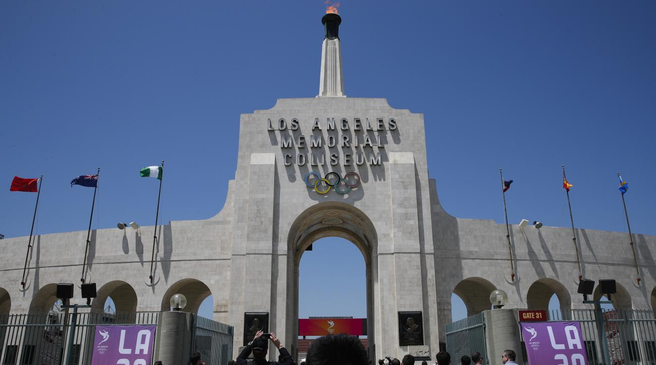 Members of the media enter the Los Angeles Memorial Coliseum, Thursday, May 11, 2017, in Los Angeles. After bidding for the 2024 Olympics, Los Angeles might have to wait. With the competition down to LA and Paris, IOC leaders are considering a proposal to