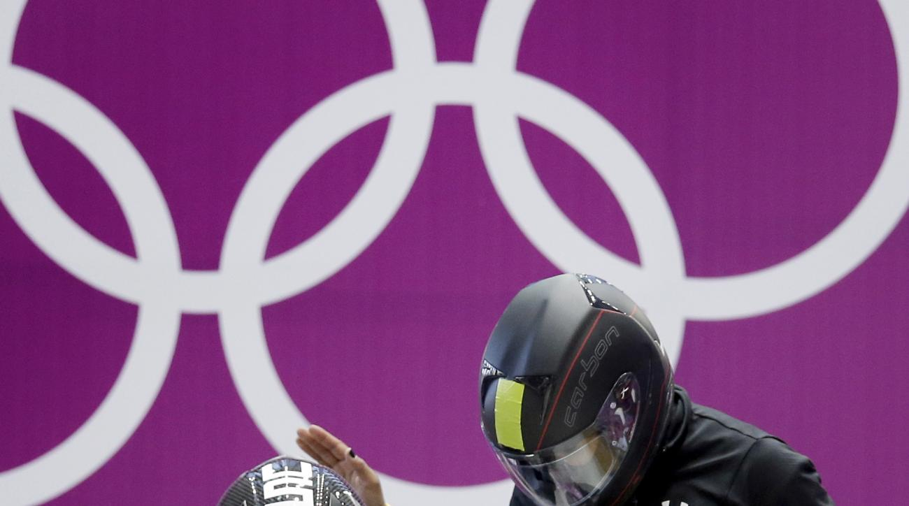 FILE - In this Feb. 14, 2014, file photo, Jazmine Fenlator, right, and Lolo Jones of the United States prepare for a heat race of the women's bobsleigh competition at the 2014 Winter Olympics, in Krasnaya Polyana, Russia. The quest for gold and America's