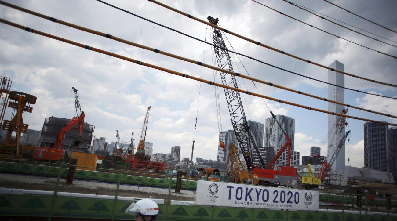 A postman rides a bike past the construction site of the athlete's village for the 2020 Tokyo Summer Olympics in Harumi in Tokyo, Friday, June 2, 2017.  The cost of the 2020 Tokyo Olympics is nearly twice the initial estimate despite a major cost-cutting