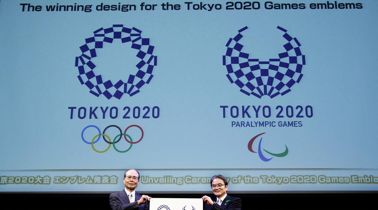 FILE - In this April 25, 2016, file photo, Tokyo 2020 Emblems Selection Committee Chairperson Ryohei Miyata, right, and its member and Japanese baseball great Sadaharu Oh hold new official logos of the 2020 Tokyo Olympics, left, and the 2020 Tokyo Paralym