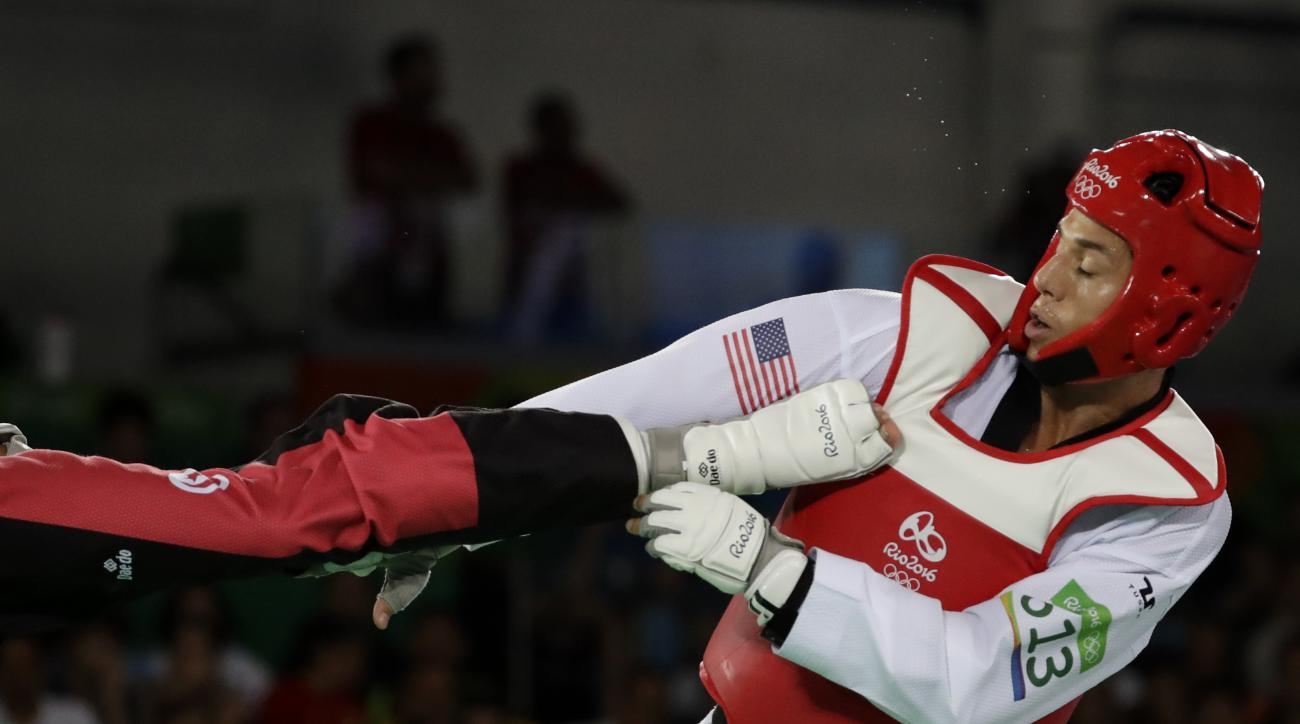 File-This Aug. 19, 2016, file photo shows Steven Lopez of the United States being kicked by Oussama Oelslati of Tunisia during a men's 80 kg taekwondo bronze medal contest at the 2016 Summer Olympics in Rio de Janeiro, Brazil.  USA Today reported Friday,