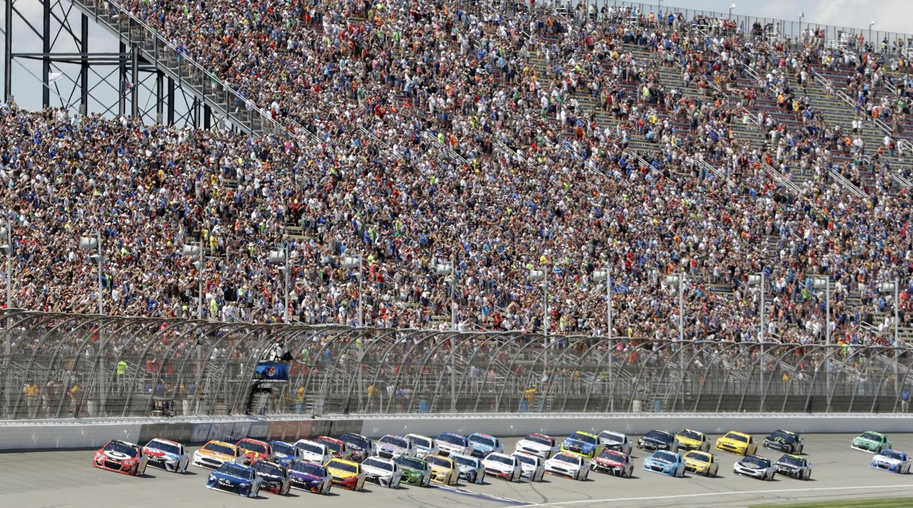Kyle Larson, front left, and Martin Truex Jr. lead the field to start a NASCAR Sprint Cup series auto race, Sunday, June 18, 2017, in Brooklyn, Mich. (AP Photo/Carlos Osorio)