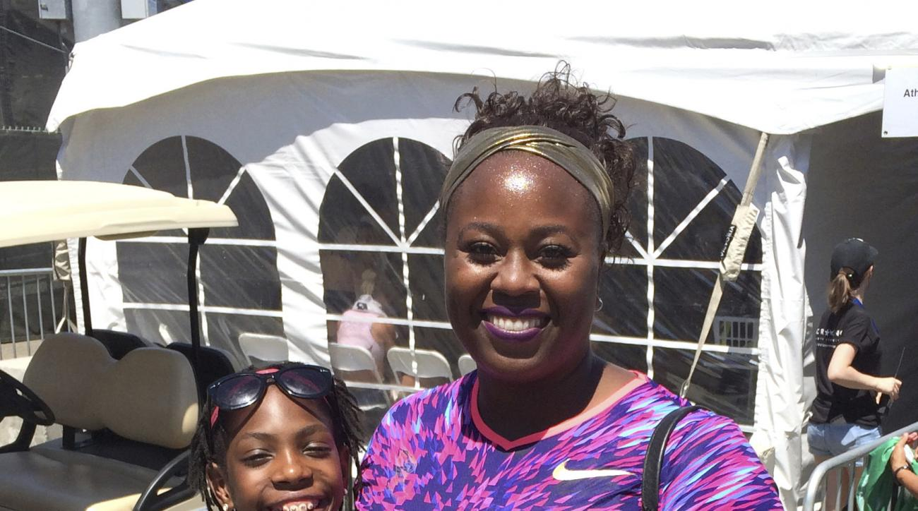 In this photo taken Saturday, June 24, 2017, Michelle Carter, who took third in the shot put, poses with Rainn Sheppard at the U.S. Track and Field Championships, in Sacramento, Calif. Rainn, 11and her sisters Tai, 12 and Brooke, 9, who were once-homeless