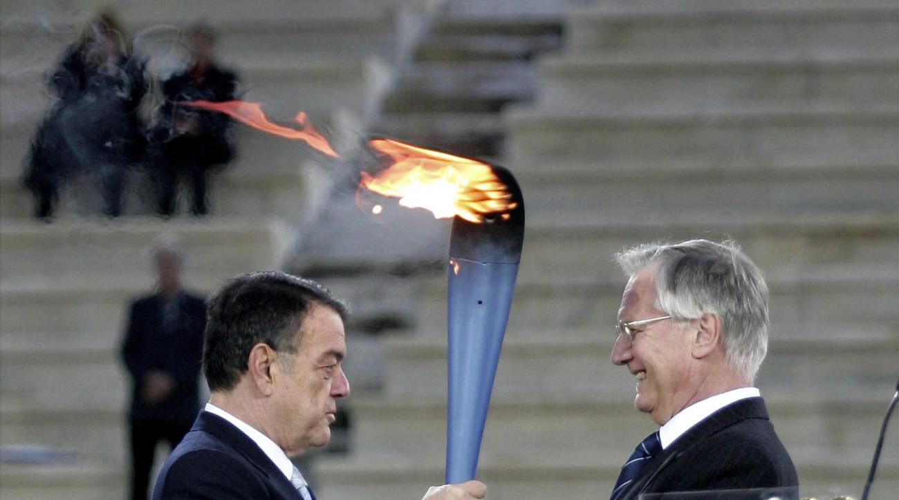 FILE - In this Dec. 6, 2005 file photo, President of the Organizing Committee for the Turin 2006 Winter Games Valentino Castellani, right, receives the Olympic flame from the President of the Greek Olympic Committee Minos Kyriakou during a ceremony at the