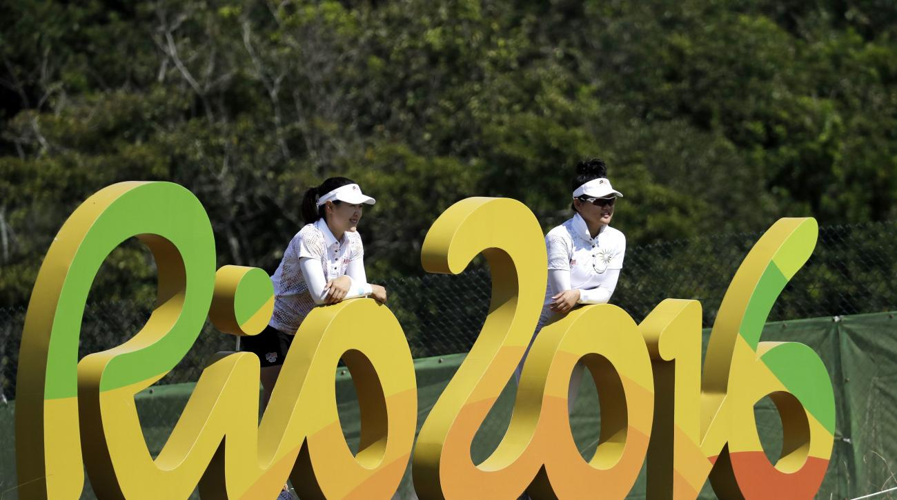 FILE - In this Aug. 16, 2016 file photo, Kelly Tan, left, and Michelle Koh, both of Malaysia, pose for a photo with the Rio 2016 logo on the 16th hole during a practice round for the women's golf event at the 2016 Summer Olympics in Rio de Janeiro, Brazil