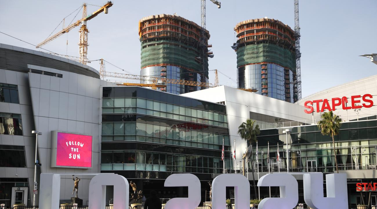 FILE- In this Thursday, May 11, 2017 file photo, a Los Angeles 2024 sign stands in front of Staples Center, in Los Angeles. An International Olympic Committee panel has praised Los Angeles and Paris for outstanding plans to host the 2024 Summer Games. (AP