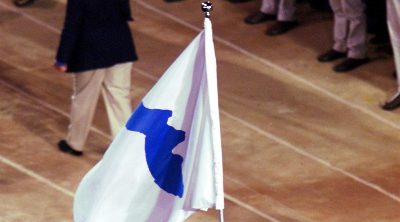 FILE - In this Sept. 15, 2000 file photo, Pak Jung Chul, left, a North Korea's Judo coach, and Chung Eun-sun, a South Korean basketball player, carry a flag representing a united Korea into Olympic Stadium during the Opening Ceremony of the Olympics in Sy