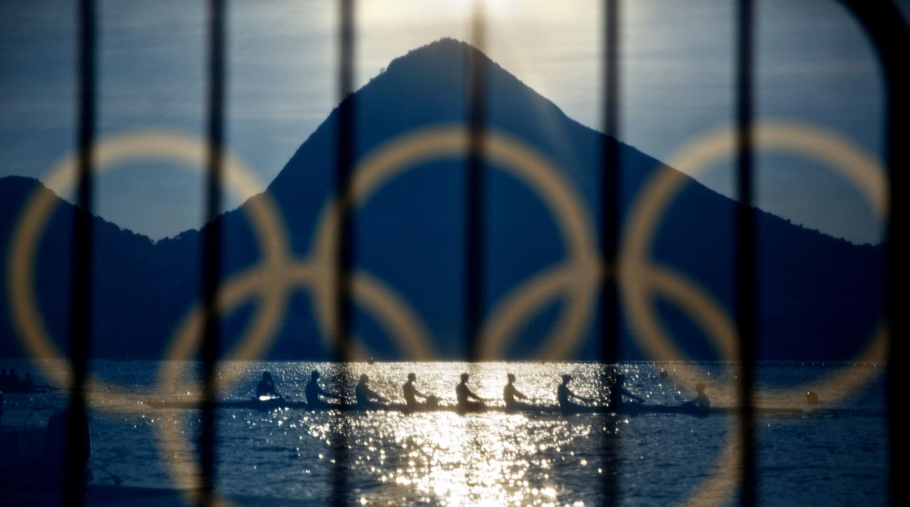 FILE - In this Aug. 7, 2016, file photo, rowers are seen through a screen decorated with the Olympic rings as they practice at the rowing venue in Lagoa at the 2016 Summer Olympics in Rio de Janeiro, Brazil. The Olympic Channel, a new Olympic-themed telev