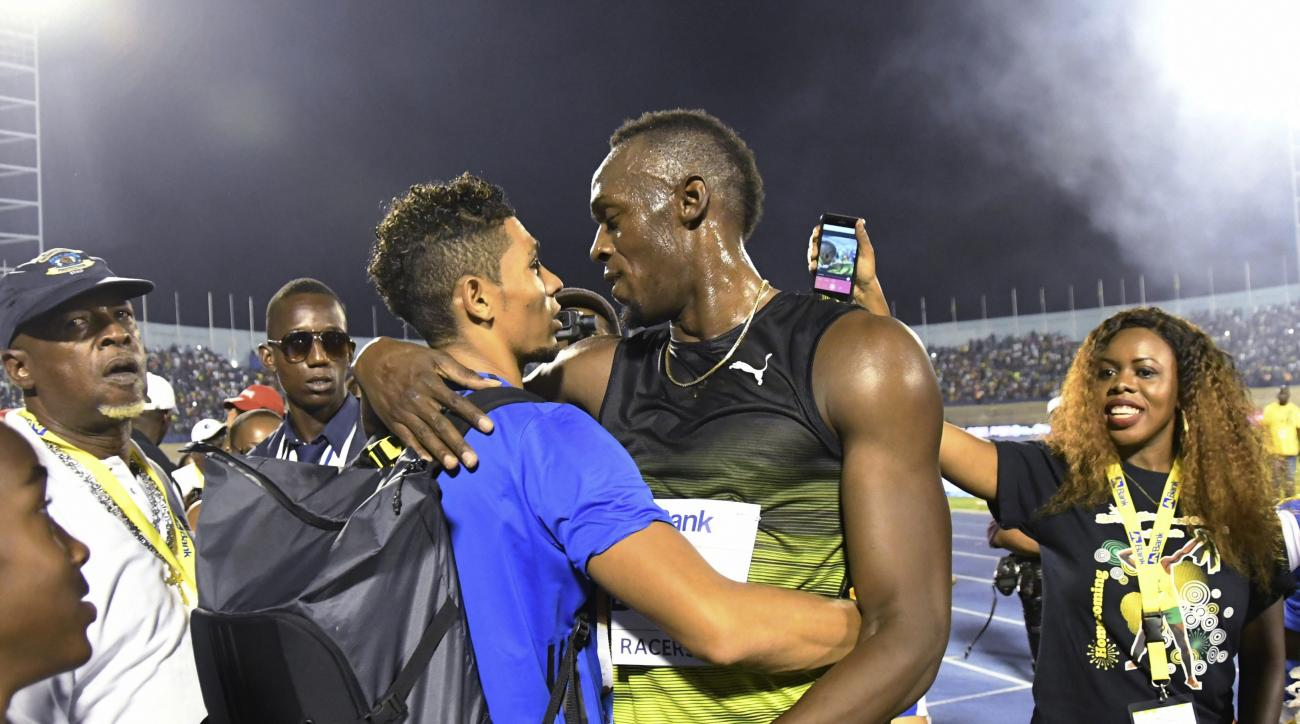 "FILE - In this file photo dated Saturday, June 10, 2017,  Jamaica's Usain Bolt, center right, embraces South African sprinter Wayde van Niekerk after winning the ""Salute to a Legend"" 100 meters during the Racers Grand Prix at the national stadium in Kings"