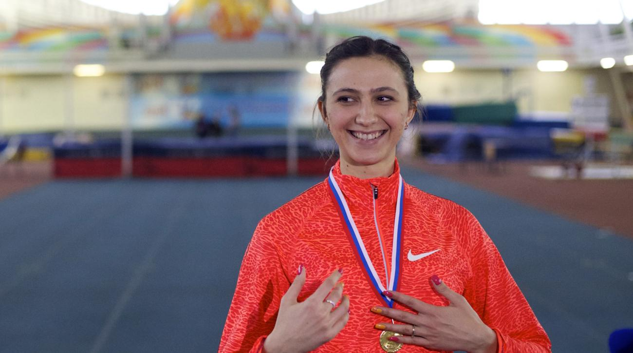 FILE - In this Friday, Jan. 22, 2016 file photo, Russia's Maria Lasitskene smiles with her gold medal after winning the women's high jump competition at a Russian Grand Prix track and field indoor event in Moscow, Russia. Russia plans to send 19 athletes,