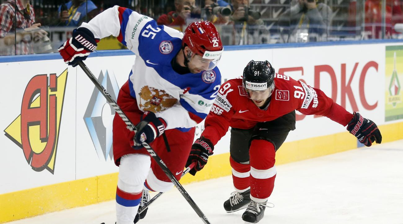 FILE - This is a Friday, May 9, 2014  file photo of Russia's Danis Zaripov, left, as he is  challenged by Switzerland's Robin Grossmann during the Group B preliminary round match between Switzerland and Russia at the Ice Hockey World Championship in Minsk