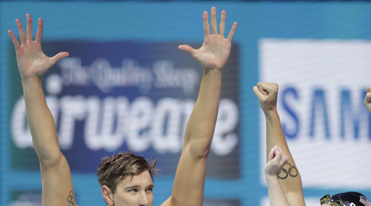 United States' Matt Grevers, Caeleb Remel Dressel and Lilly King, from left, celebrate after winning the gold medal in the mixed medley relay during the swimming competitions of the World Aquatics Championships in Budapest, Hungary, Wednesday, July 26, 20