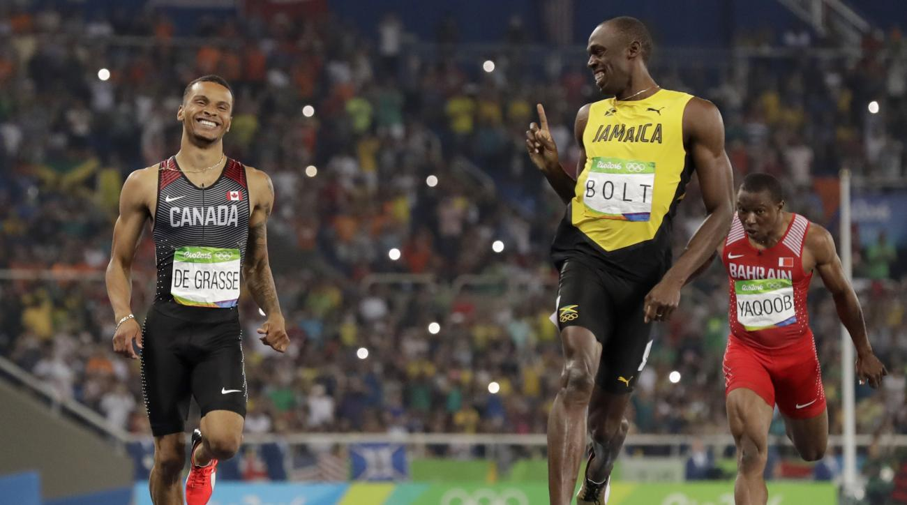 FILE - In this Aug. 17, 2016, file photo, Jamaica's Usain Bolt, right, gestures towards Canada's Andre De Grasse after the finish of the men's 200-meter semifinal during the athletics competitions of the 2016 Summer Olympics at the Olympic stadium in Rio