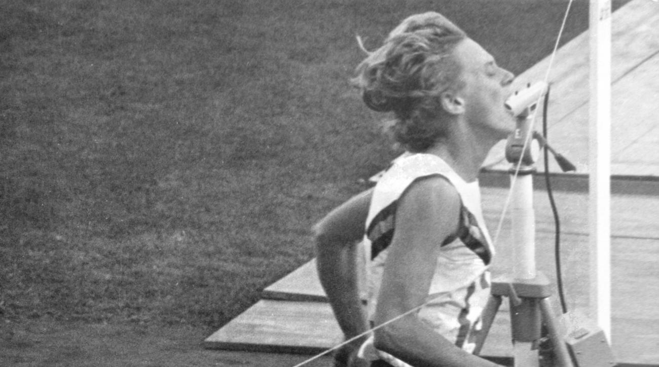 FILE - In this file photo dated Oct. 17, 1964, Australia's Betty Cuthbert crosses the finish line to win the Olympic women's 400 meters race at the National Stadium in Tokyo.  Betty Cuthbert, the only runner to win Olympic gold medals in the 100-, 200- an