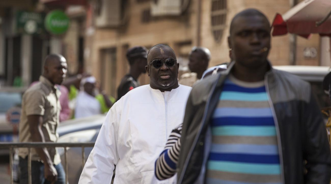 FILE - In this Feb. 17, 2016, file photo, Papa Massata Diack, center, son of former IAAF President Lamine Diack, arrives at the central police station in Dakar, Senegal. Life bans for the son of former IAAF President Lamine Diack and Russia's former top t