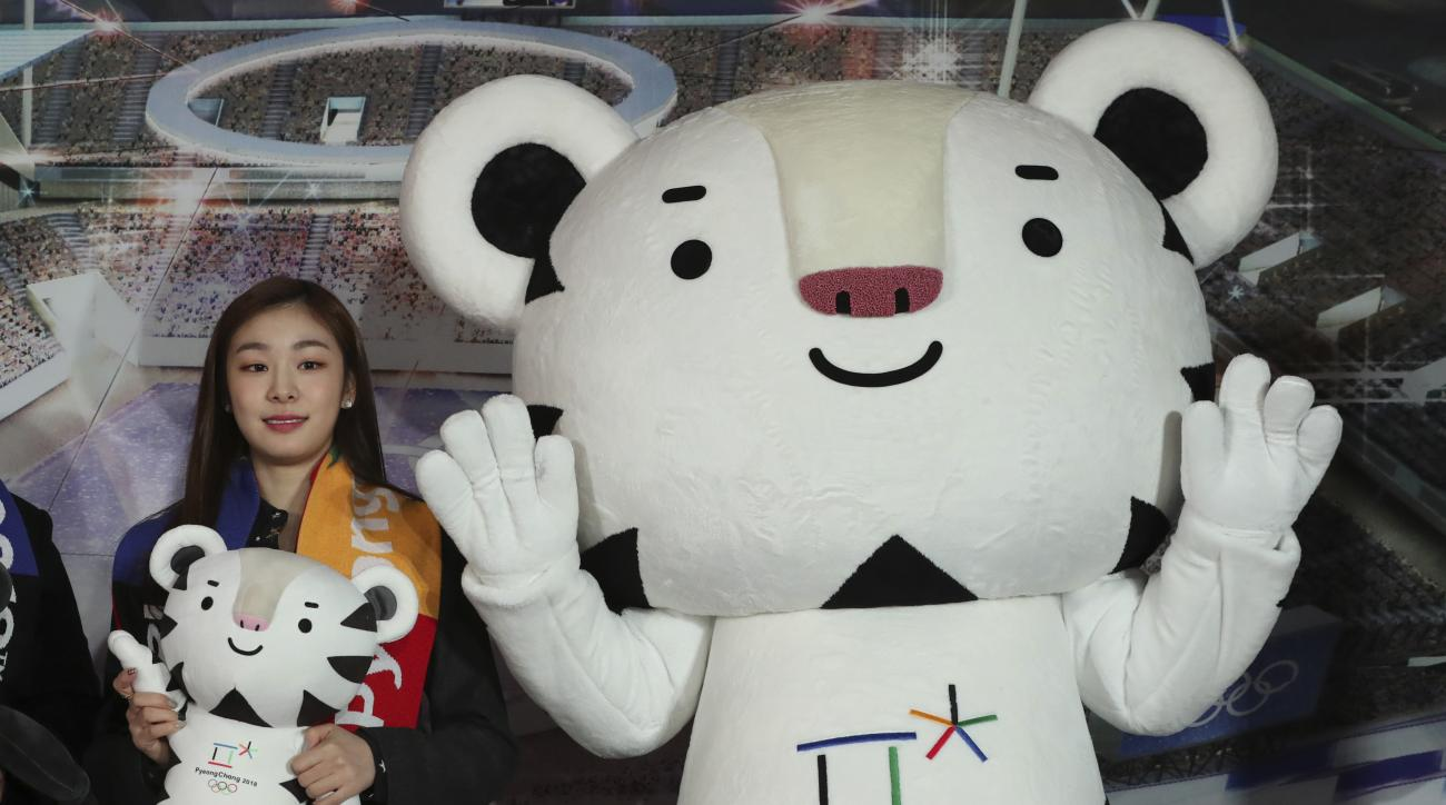 "FILE - In this Feb. 9, 2017, file photo, figure skating Olympics gold medalist Yuna Kim, an honorary ambassador for the 2018 Winter Olympics, poses with an official mascot of the 2018 Pyeongchang Olympic Winter Games, white tiger ""Soohorang,"" at Gangneung"