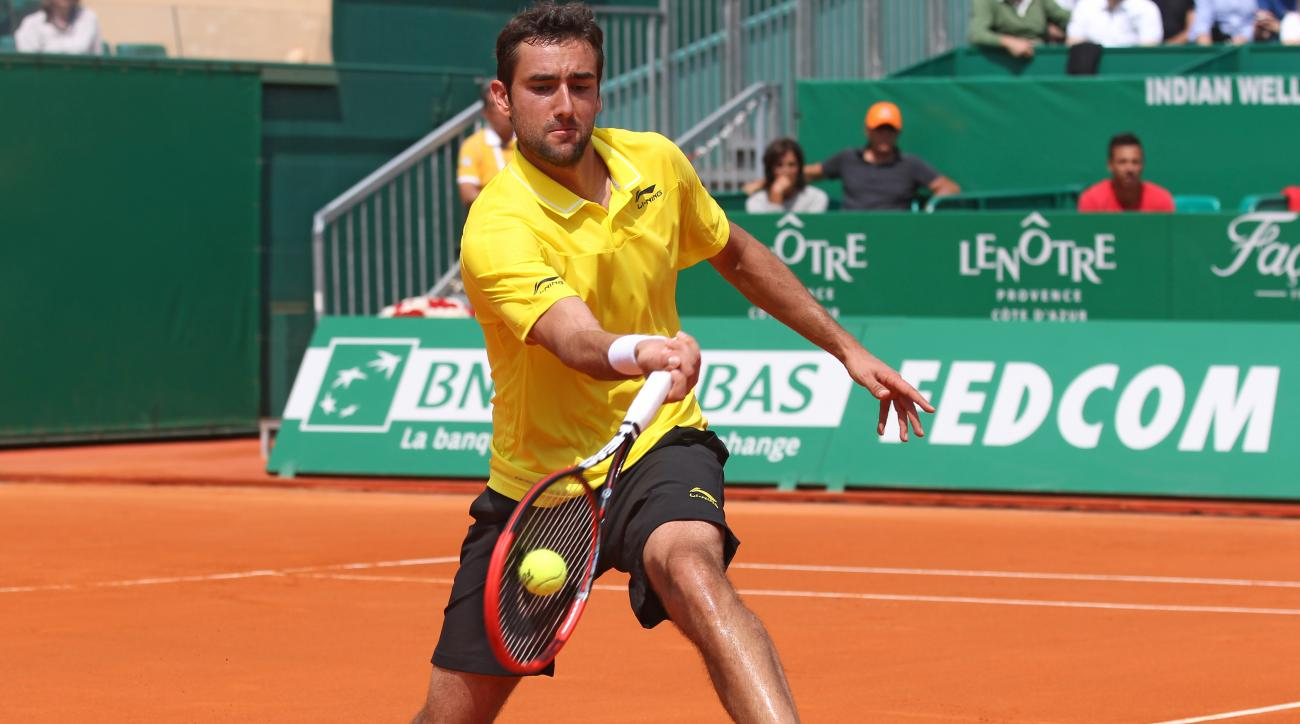 Marin Cilic of  Croatia plays a return to Novak Djokovic of Serbia during their quarterfinal match of the Monte Carlo Tennis Masters tournament in Monaco, Friday, April 17 2015. (AP Photo/Lionel Cironneau)