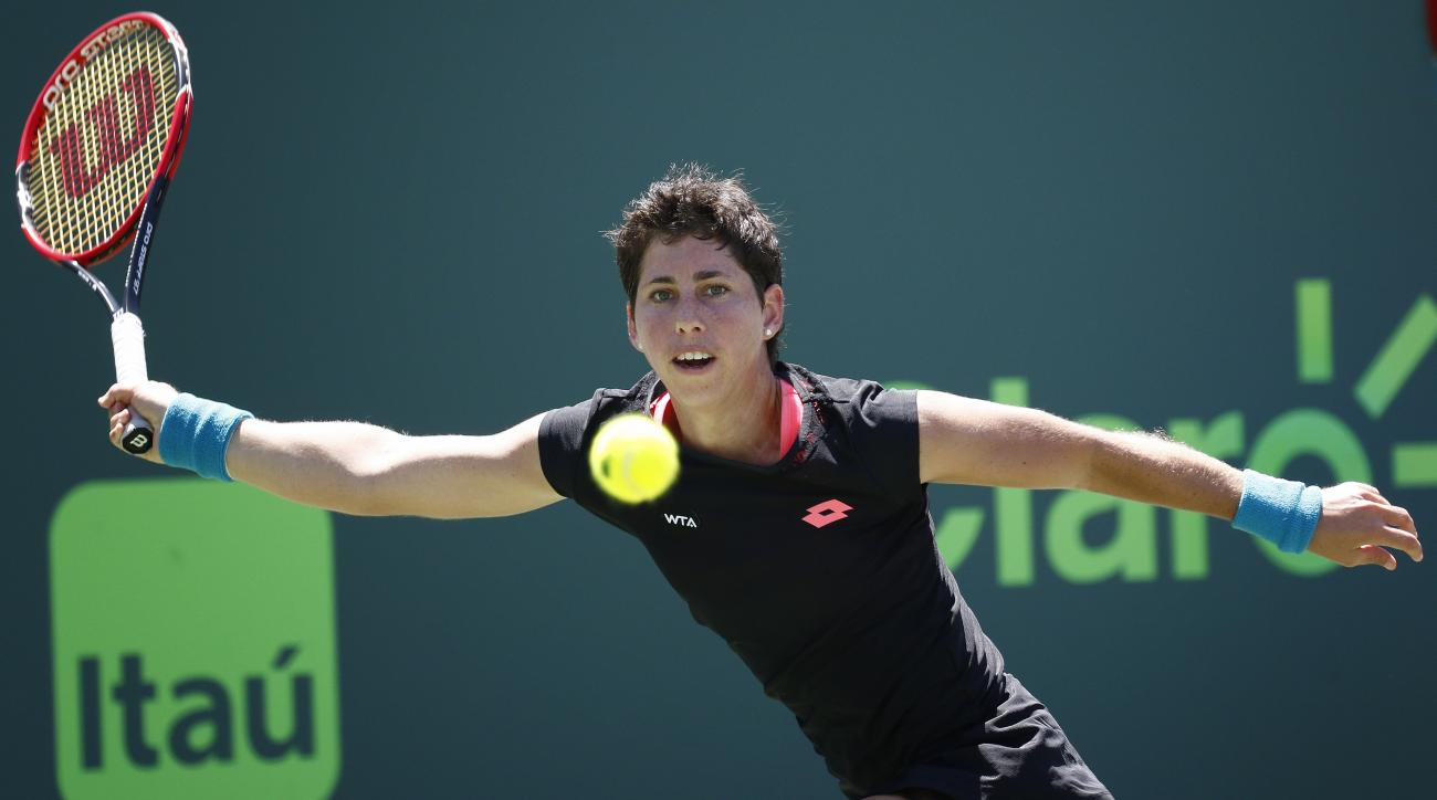 Carla Suarez Navarro, of Spain, chases the ball as she tries to return it to Serena Williams during the women's final at the Miami Open tennis tournament in Key Biscayne, Fla., Saturday, April 4, 2015. Williams won 6-2, 6-0. (AP Photo/J Pat Carter)