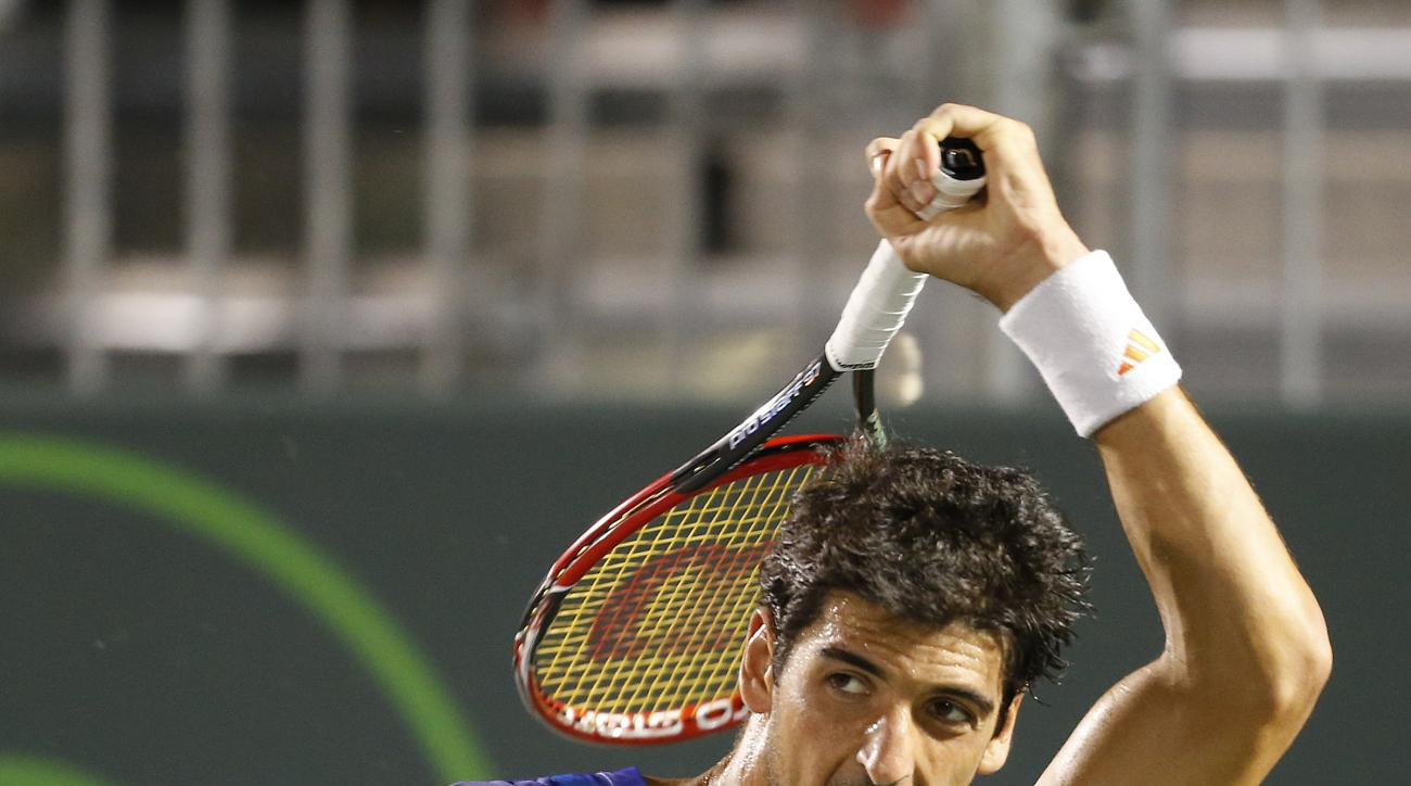 Thomaz Bellucci, of Brazil, returns the ball to Pablo Cuevas, of Uruguay, at the Miami Open tennis tournament in Key Biscayne, Fla., Saturday, March 28, 2015. (AP Photo/Joel Auerbach)