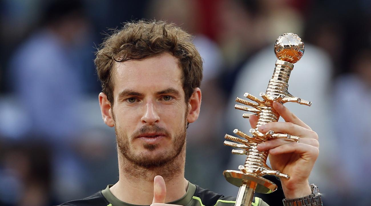 Andy Murray of Britain holds up the winners trophy after defeating Rafael Nadal of Spain in their men's singles final match at the Madrid Open Tennis tournament in Madrid, Spain, Sunday, May 10, 2015.  Murray defeated Nadal 6-3, 6-2. (AP Photo/Paul White)