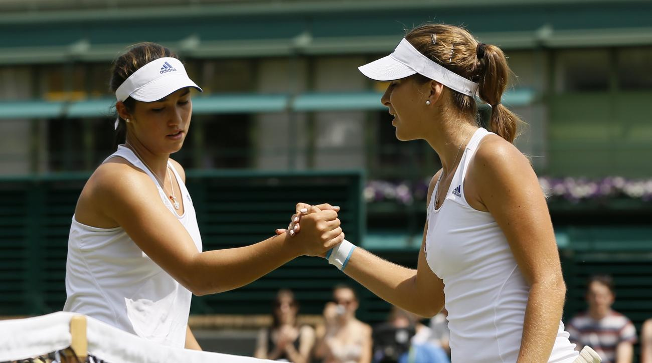Switzerland's Belinda Bencic, right, greets Louisa Chirico of the United States at the net after winning their Girls Singles semifinal match at the All England Lawn Tennis Championships in Wimbledon, London, Friday, July 5, 2013. (AP Photo/Kirsty Wigglesw