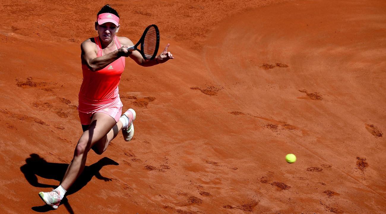 Romania's Simona Halep strikes a forehand to Spain's Carla Suarez Navarro, during their semifinal match at the Italian Open tennis tournament, in Rome, Saturday, May 16, 2015. (Claudio Onorati/ANSA via AP)