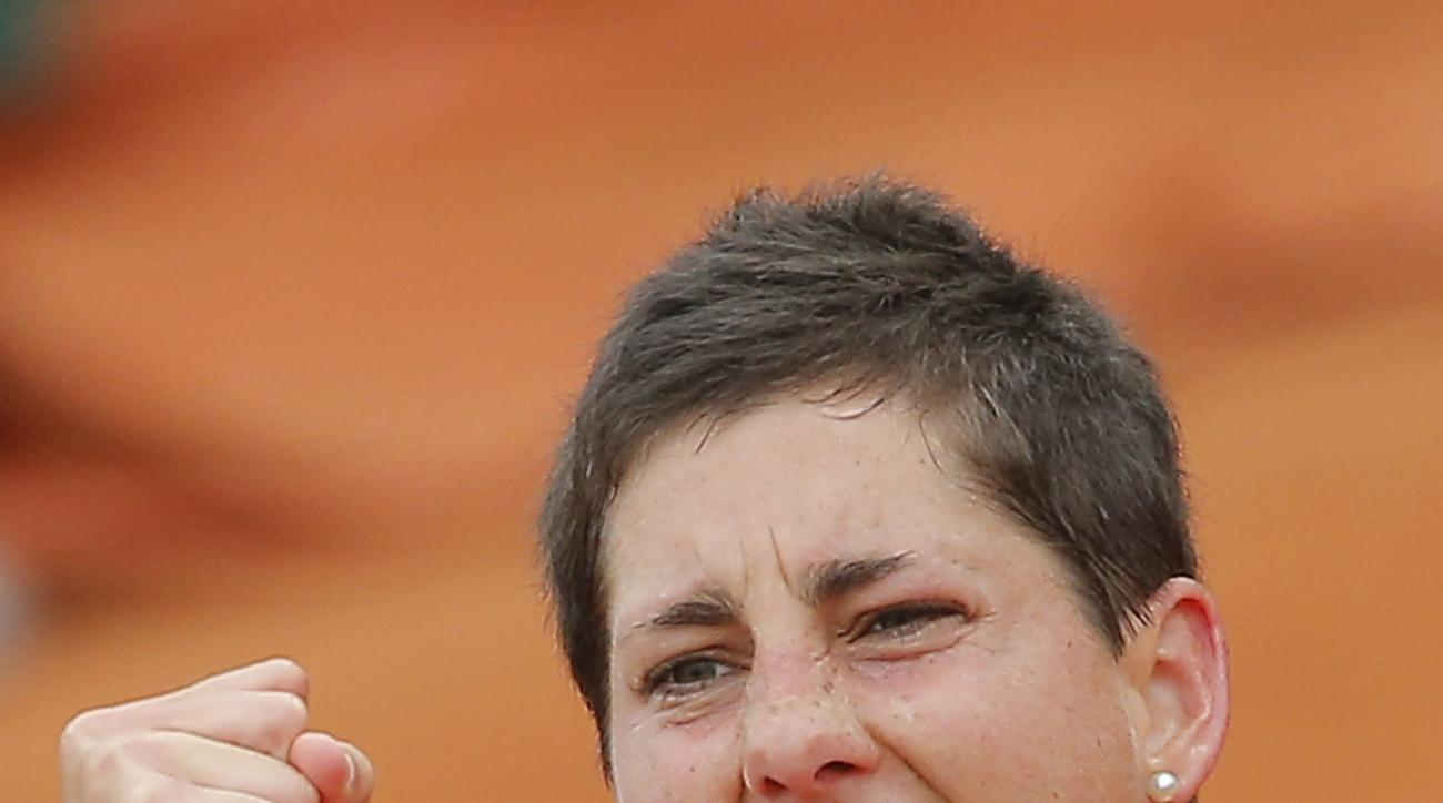 FILE - In this June 1, 2014, file photo, Spain's Carla Suarez Navarro celebrates winning a fourth round match against Croatia's Ajla Tomljanovic at the French Open tennis tournament in Paris, France. Navarro will be competing in the 2015 French Open tenni