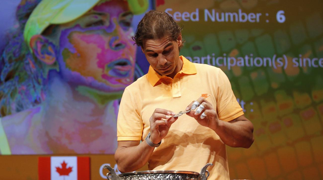 Defending champion Spain's Rafael Nadal picks a token during the draw for the French Tennis Open at the Roland Garros stadium, Friday, May 22, 2015 in Paris. Player on screen behind is Canada's Eugenie Bouchard. The French Open starts Sunday. (AP Photo/Fr