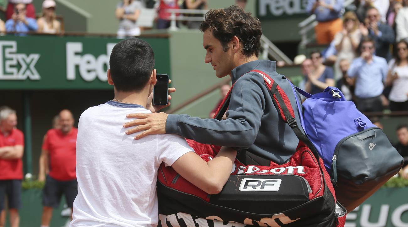 A boy who climbed down from the stands takes a selfie with Switzerland's Roger Federer in the first round match of the French Open tennis tournament against Colombia's Alejandro Falla at the Roland Garros stadium, in Paris, France, Sunday, May 24, 2015. (