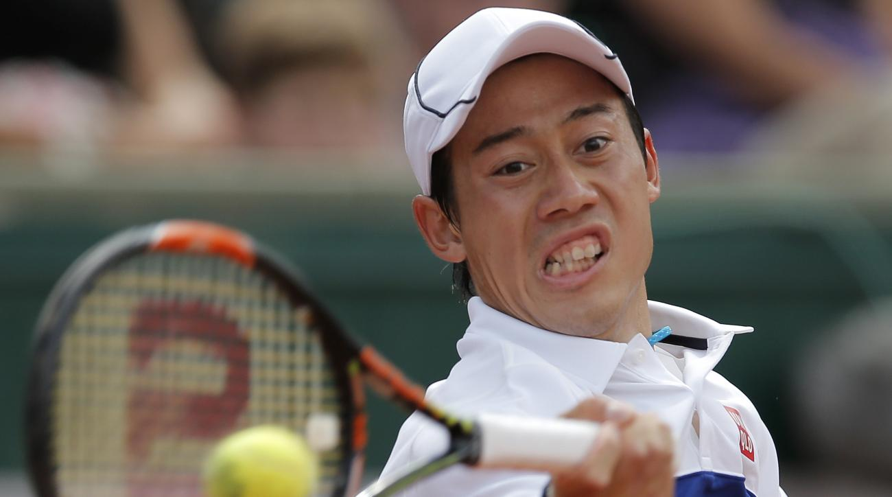 Japan's Kei Nishikori returns the ball to France's Paul-Henri Mathieu during their first round match of the French Open tennis tournament at the Roland Garros stadium, Sunday, May 24, 2015 in Paris,  (AP Photo/Christophe Ena)