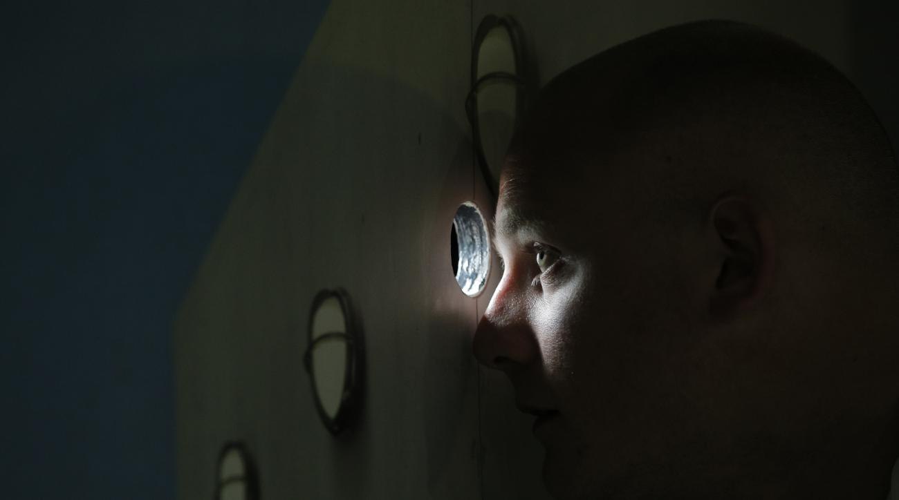 A security officer watches through a hole in the door for a break between games to let photographers into the stadium as Serbia's Ana Ivanovic plays in the first round match of the French Open tennis tournament against Yaroslava Shvedova of Kazakhstan at