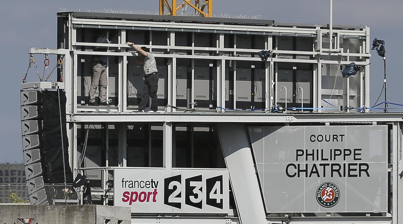 Two men work on the backside of a giant TV screen after a large piece of paneling fell on spectators at center court during the quarterfinal match of the French Open tennis tournament against at the Roland Garros stadium, in Paris, France, Tuesday, June 2