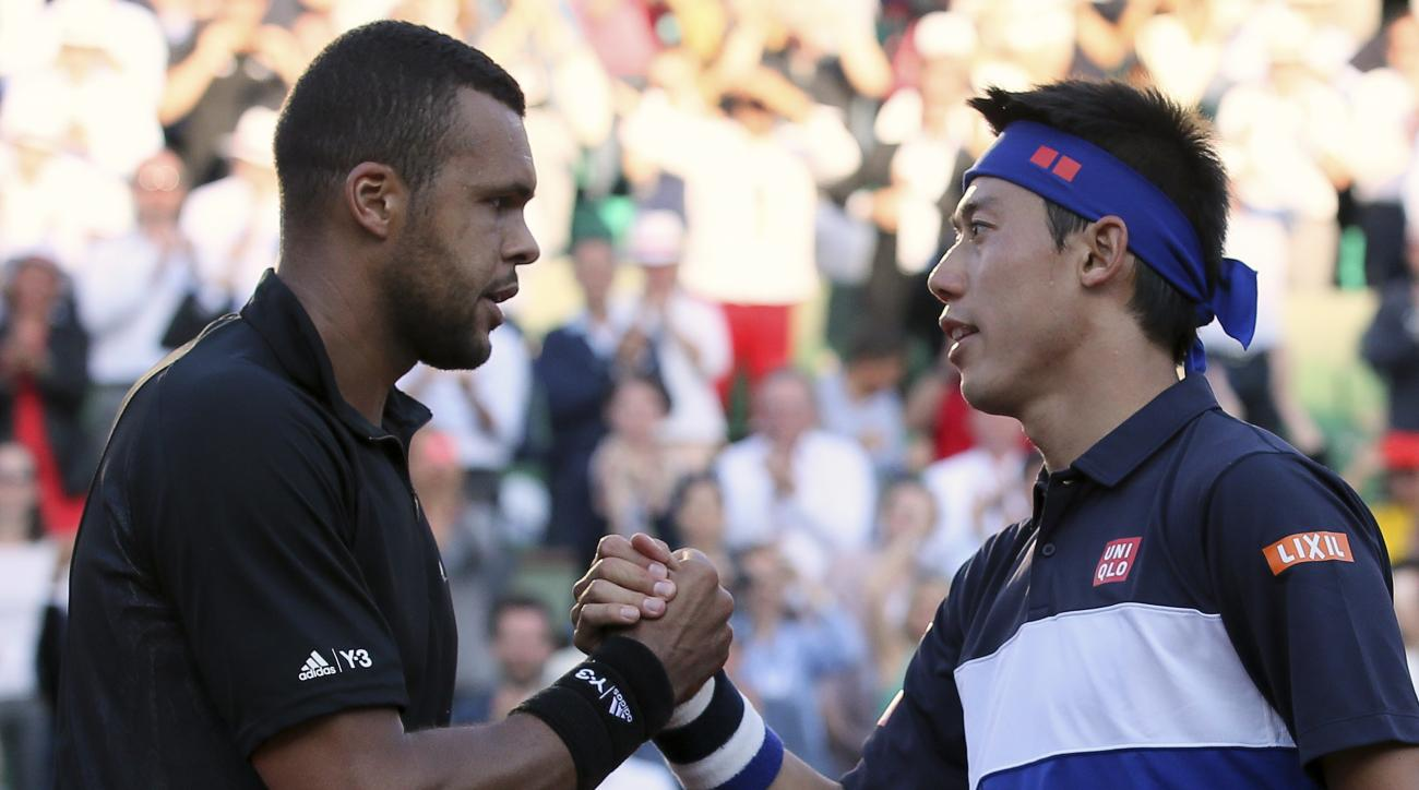 France's Jo-Wilfried Tsonga shakes hands with Japan's Kei Nishikori after winning in the quarterfinal match of the French Open tennis tournament in five sets 6-1, 6-4, 4-6, 3-6, 6-3, at the Roland Garros stadium, in Paris, France, Tuesday, June 2, 2015. (
