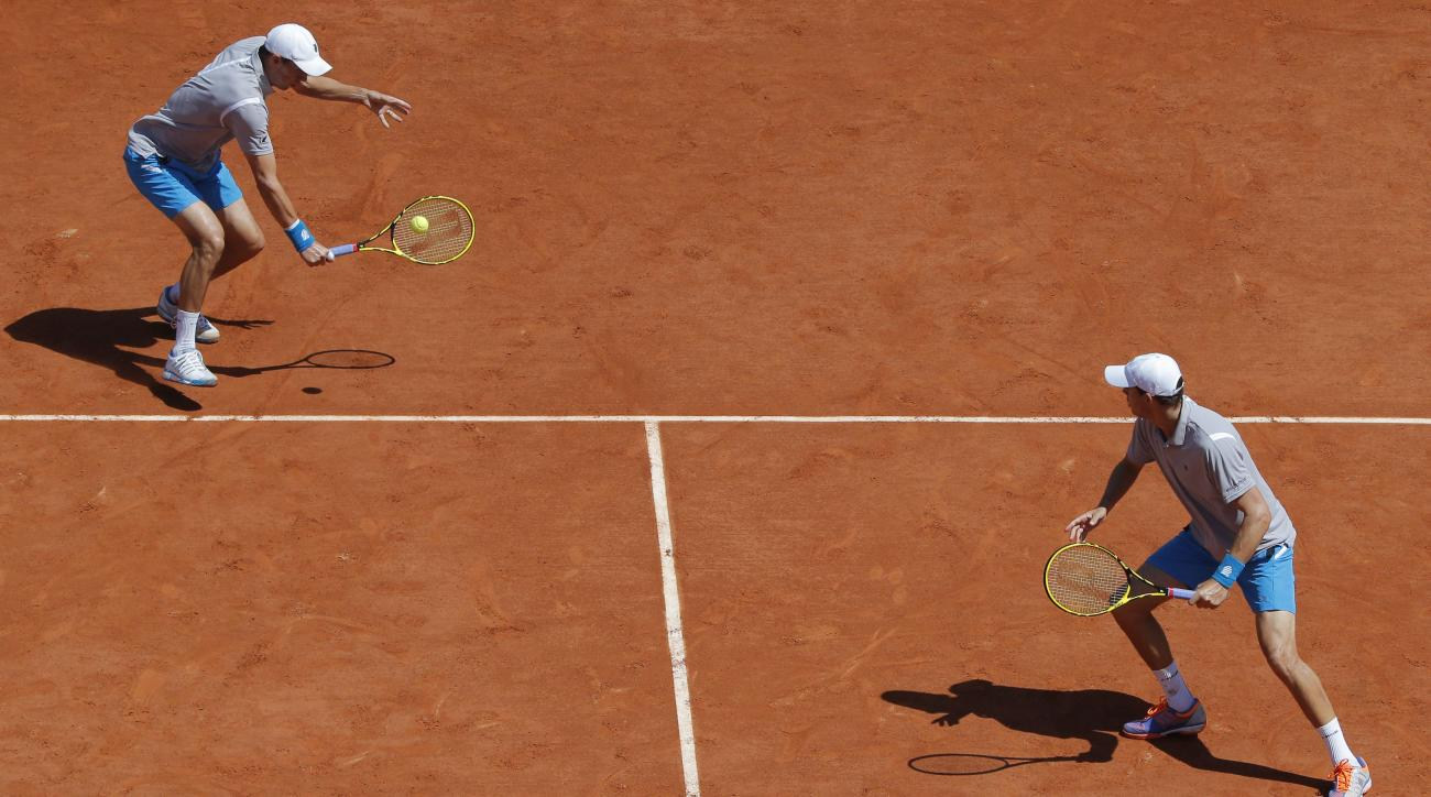 Bob, right, and Mike Bryan of the U.S. return in the men's double semifinal match of the French Open tennis tournament against Italy's Simone Bolelli and Fabio Fognini at the Roland Garros stadium, in Paris, France, Thursday, June 4, 2015. (AP Photo/Chris