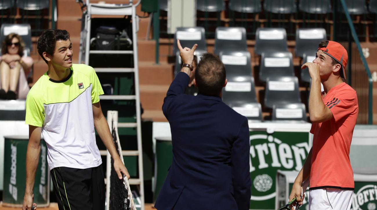 Taylor Harry Fritz, left, and Tommy Paul of the U.S. watch the toss of the coin at the start of the boy's final match of the French Open tennis tournament at the Roland Garros stadium, in Paris, France, Saturday, June 6, 2015. (AP Photo/Thibault Camus)